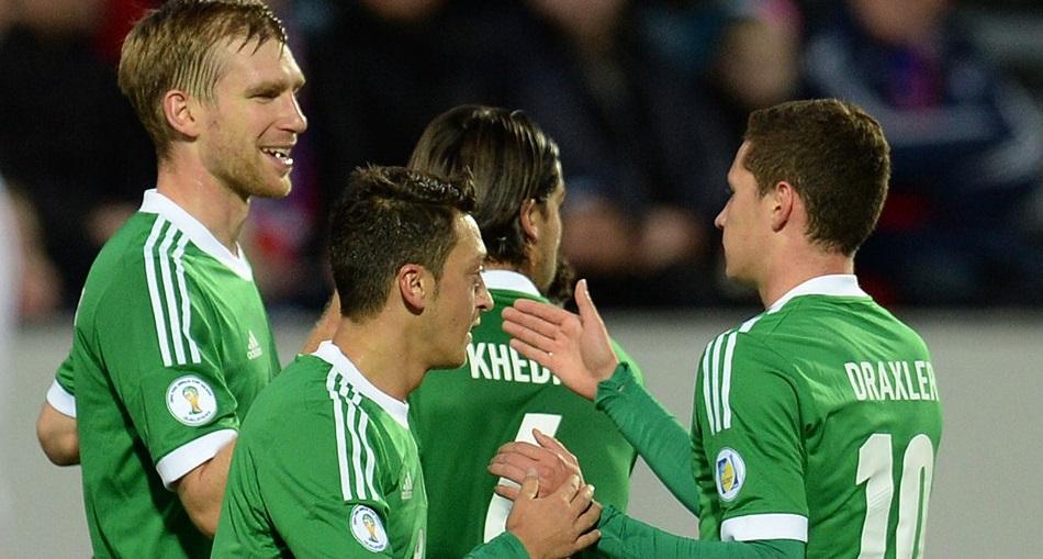 Ozil a mais recente negociação europeia entre Arsenal e Real Madri marcou o segundo gol da vitória alemã, que reeditou seu tradicional uniforme verde. (Foto: AFP)