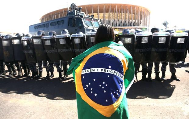 Manifestante se posiciona a frente do cordão de isolamento da PM em Brasília. (Foto: EFE).